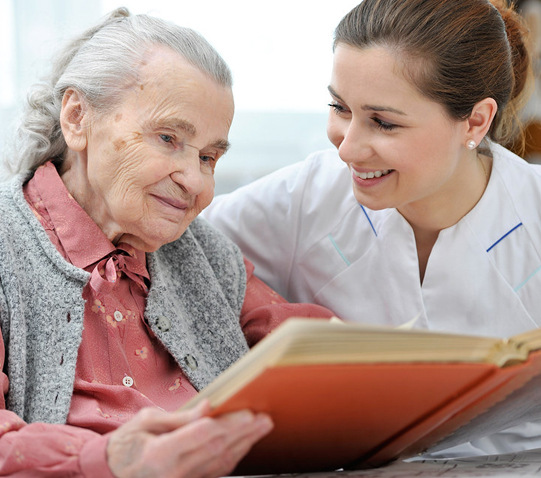 stock photo of elderly woman reading with an attendant